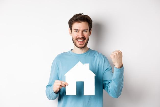Conceito imobiliário e seguro. homem alegre comprando uma propriedade e comemorando, dizendo sim e mostrando o recorte da casa de papel, de pé sobre um fundo branco.
