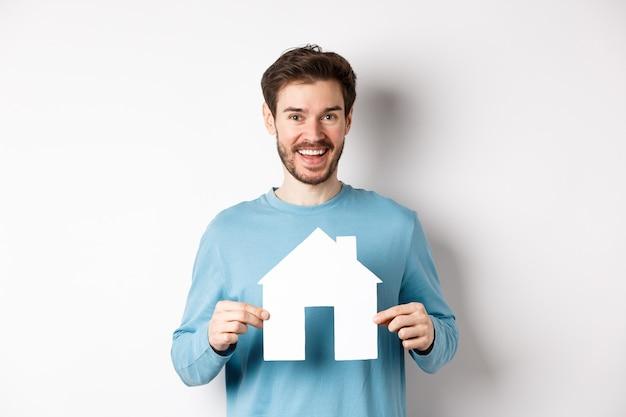 Conceito imobiliário e seguro. homem bonito e moderno comprando uma propriedade, sorrindo e mostrando o recorte da casa de papel, em pé sobre um fundo branco