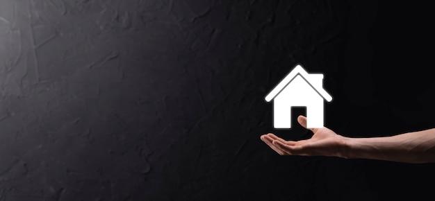 Conceito imobiliário, empresário segurando um ícone de casa. casa disponível. conceito de seguro e segurança de propriedade. protegendo o gesto do homem e o símbolo da casa