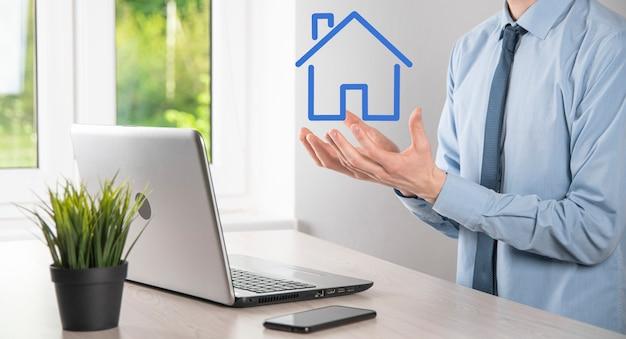 Conceito imobiliário, empresário segurando um ícone de casa. casa disponível. conceito de seguro e segurança de propriedade. protegendo o gesto do homem e o símbolo da casa.