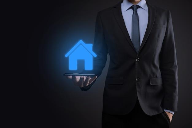 Conceito imobiliário, empresário segurando um ícone de casa