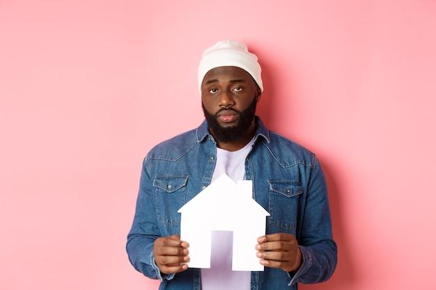 Conceito imobiliário. homem negro triste e cansado olhando desinteressado para a câmera, segurando uma modelo de casa de papel, em pé sobre um fundo rosa