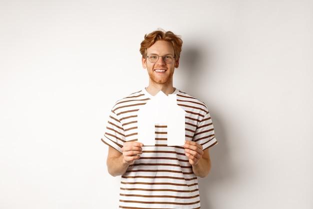 Conceito imobiliário. homem ruivo sorridente de óculos segurando a casa de papel recortado e olhando para a câmera, economizando para comprar um imóvel, em pé sobre um fundo branco.
