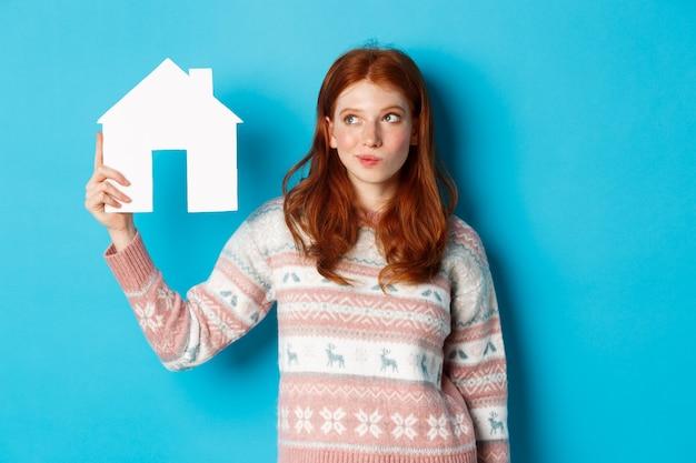 Conceito imobiliário. imagem de uma ruiva pensativa mostrando o modelo de uma casa de papel e pensando, procurando por uma casa ou apartamento, em pé contra um fundo azul