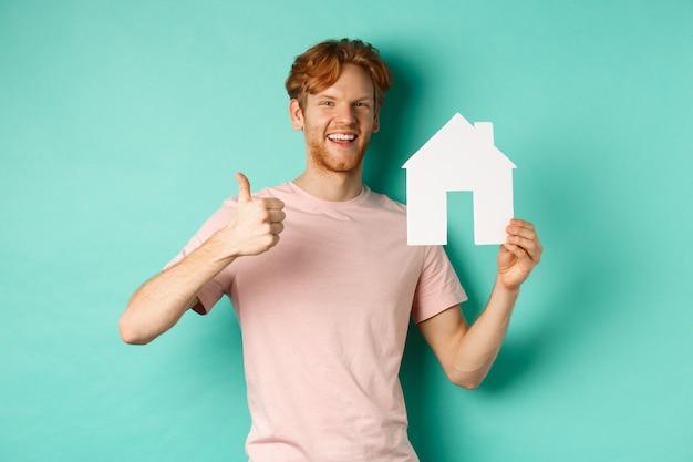 Conceito imobiliário. jovem ruivo, vestindo camiseta, mostrando o recorte da casa de papel e o polegar para cima