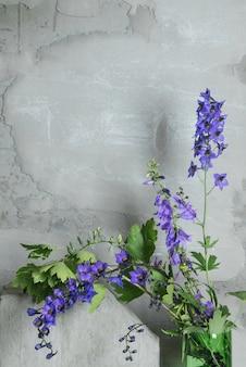 Conceito interior moderno contemporâneo. parede vazia de cimento cinza e flor violeta roxa em cima da mesa. interior de estilo loft.