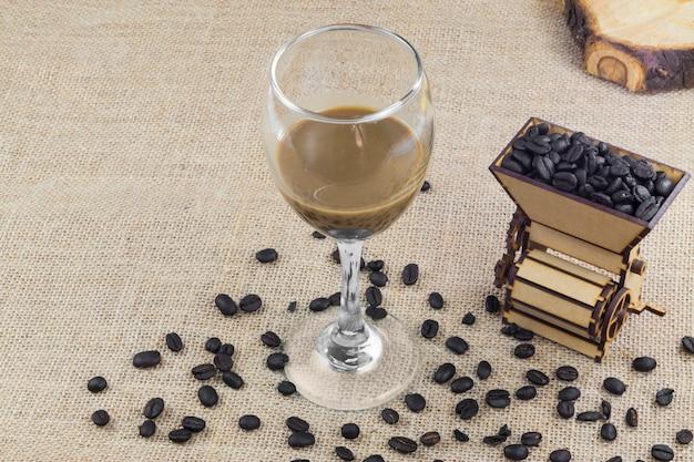 Conceito isolado de café colombiano com uma máquina de moer, grãos de café e uma xícara de creme de café