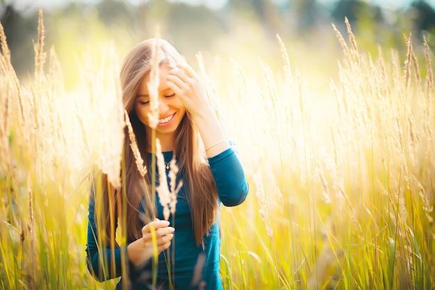 Conceito jovem bonita feliz sorridente caucasiana loira grávida em pé na sala de estar