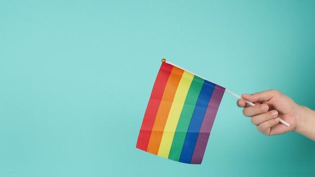 Conceito lgbt. mão está segurando uma bandeira do arco-íris em fundo verde menta ou azul tiffany.