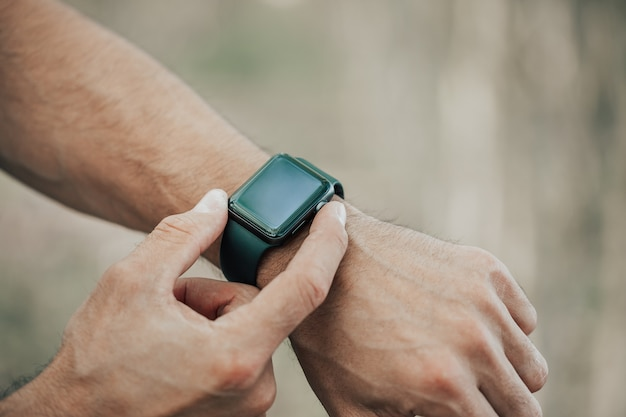 Conceito macro de homem clicando, apontando em uma tela de seu relógio inteligente de design genérico