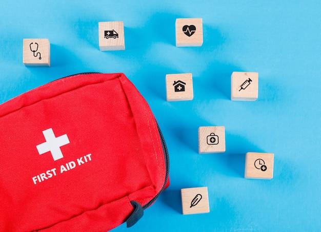Conceito médico com blocos de madeira com ícones, bolsa de primeiros socorros na mesa azul plana leigos.