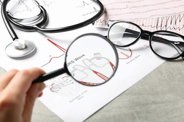 Conceito médico com lupa e eletrocardiograma, close-up