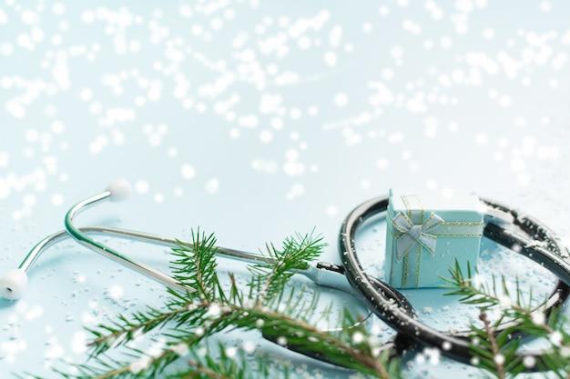 Conceito médico de natal com caixa de presente de estetoscópio e árvore de natal em azul