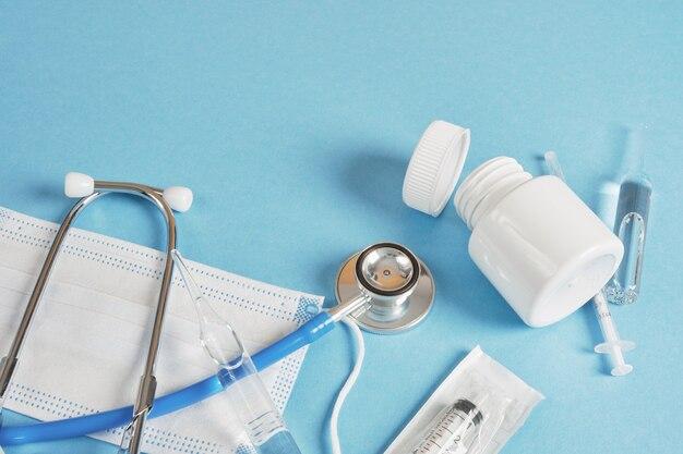 Conceito médico de tempo de saúde. comprimidos, máscara facial, ampola, seringa com estetoscópio em um fundo azul cópia do espaço vista superior