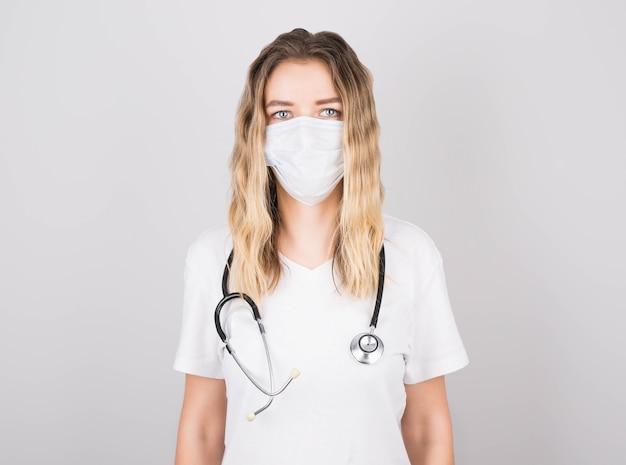 Conceito médico do médico de mulher bonita com jaleco branco com estetoscópio, máscara. estudante de medicina. mulher trabalhadora de hospital e sorridente parede cinza