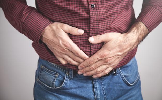 Conceito médico e de saúde homem caucasiano com dor de barriga em casa