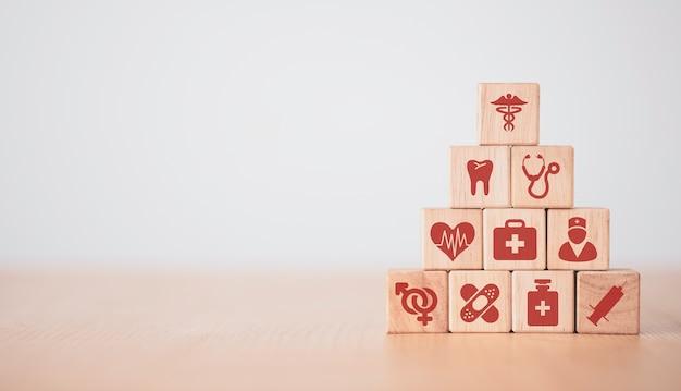 Conceito médico e hospitalar de saúde, mão colocando e empilhando cubos de bloco de madeira que imprimem ícones de saúde de tela na mesa com espaço de cópia.