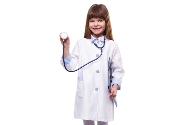 Conceito médico. fofinho sorridente garotinha médica vestindo jaleco branco com estetoscópio segurando uma pasta no fundo branco isolado
