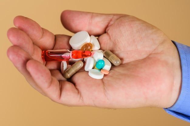 Conceito médico. mãos de homem com diferentes comprimidos prescritos pelo médico. comprimidos na mão do paciente.