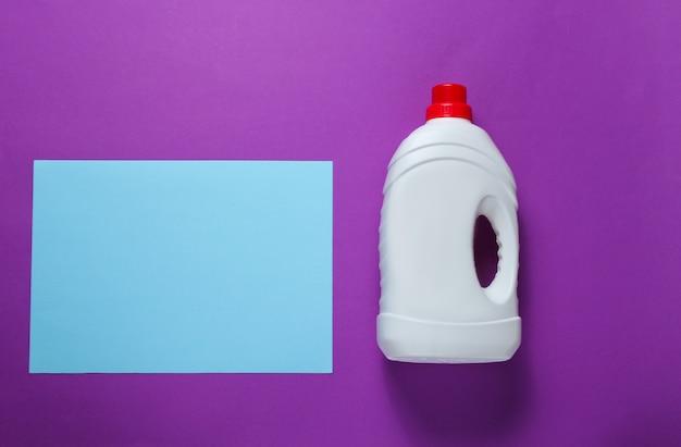 Conceito minimalista de lavagem. folha de papel azul para espaço de cópia, frasco de gel de lavagem na mesa roxa. vista do topo