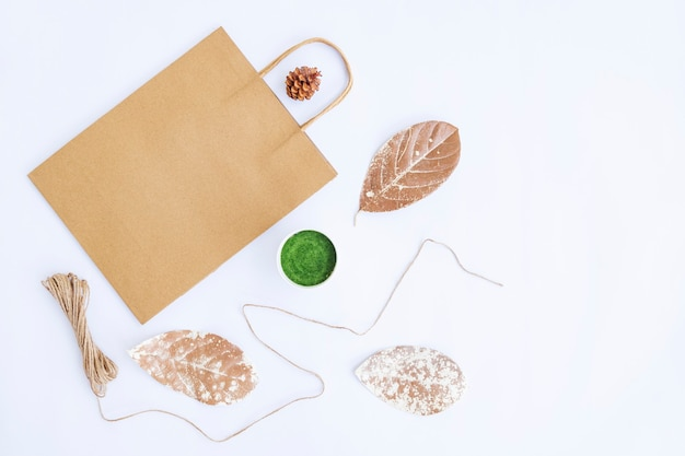 Conceito minimalista do outono. saco de papel, vaso de flores, fio de serapilheira isolado no fundo de papel branco