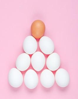 Conceito minimalista. pirâmide de ovos na mesa-de-rosa. a ideia de singularidade, pirâmide social