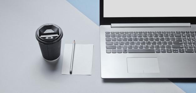 Conceito mínimo de espaço de trabalho. caderno, folha de papel com um lápis, recipiente de papelão com café em fundo cinza azulado