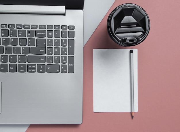 Conceito mínimo de espaço de trabalho. caderno, folha de papel com um lápis, recipiente de papelão com café em fundo cinza vermelho