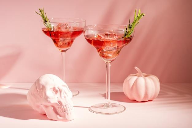 Conceito mínimo de halloween com caveira de abóbora rosa e coquetéis