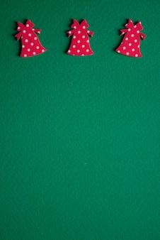 Conceito mínimo de natal. sinos vermelhos em papel texturizado verde. fechar-se.