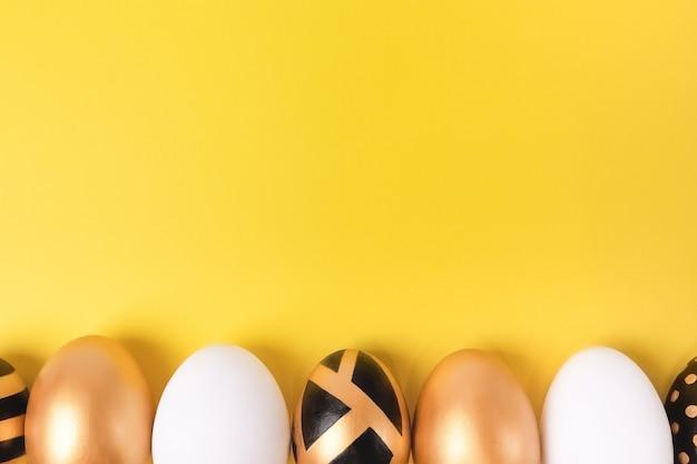 Conceito mínimo de páscoa. ovos de páscoa de ouro sobre fundo amarelo.