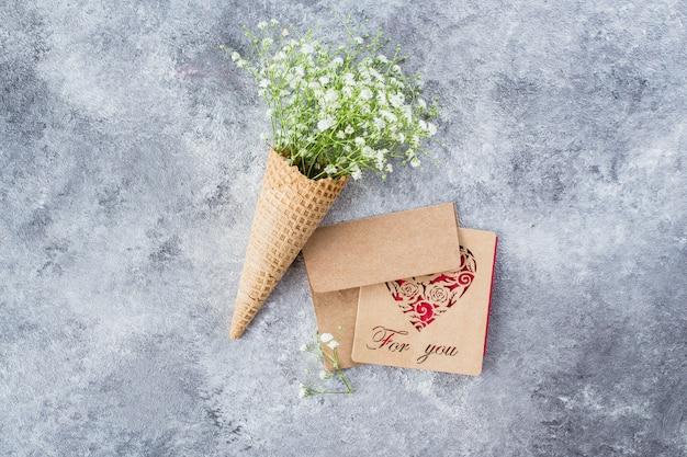 Conceito mínimo de primavera. cone do waffle com flores do gypsophila. conceito de dia da mulher mãe.
