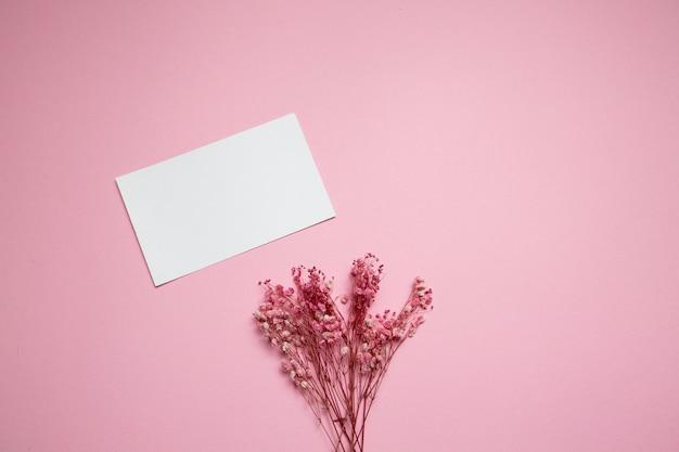 Conceito mínimo de primavera flores cor de rosa plana lay bloco de notas branco em branco