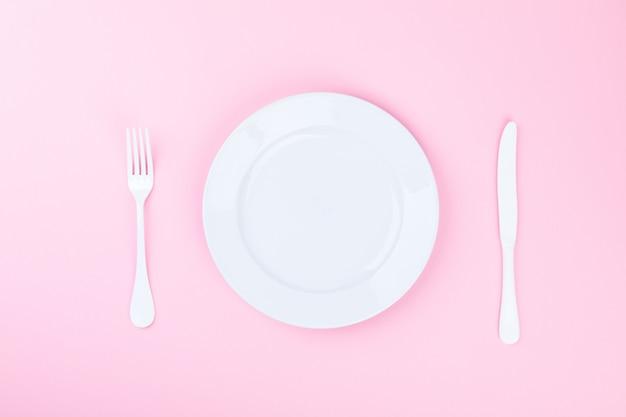Conceito mínimo. hora de comer. garfo, faca e chapa branca