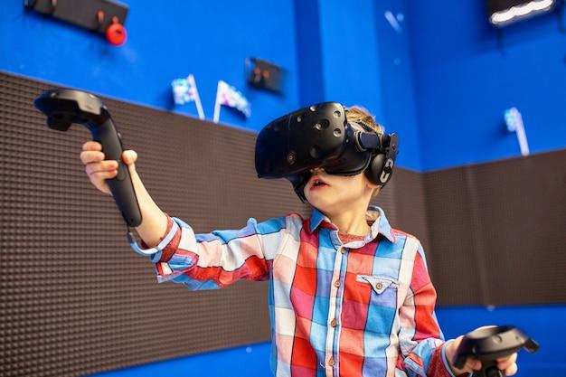 Conceito moderno de tecnologia, jogos e pessoas - menino no fone de ouvido da realidade virtual ou óculos 3d jogando videogame no game center