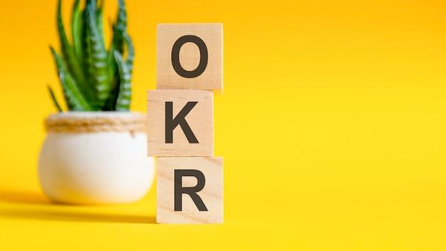 Conceito okr com blocos de madeira na mesa, fundo amarelo