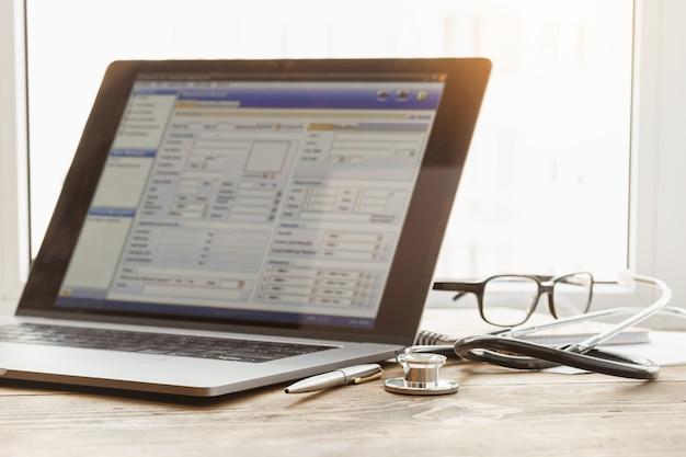 Conceito on-line de consulta médica. laptop com estetoscópio e documento