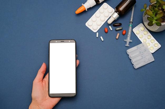 Conceito on-line de farmácia e drogaria. comprimidos de medicamento e smartphone em azul