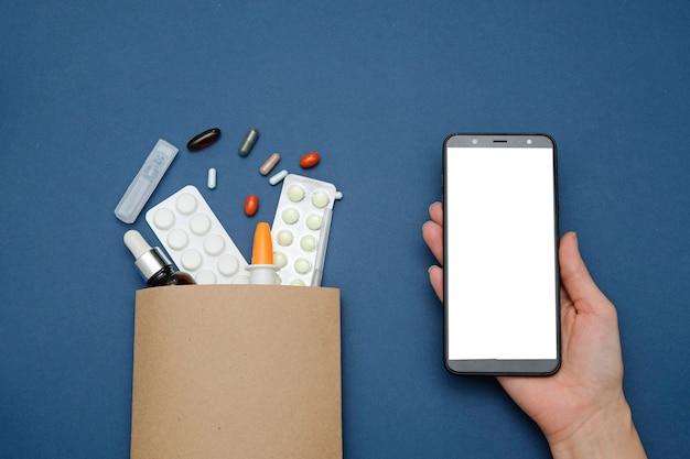 Conceito on-line de farmácia e drogaria. comprimidos de medicamento em um saco de papel e smartphone