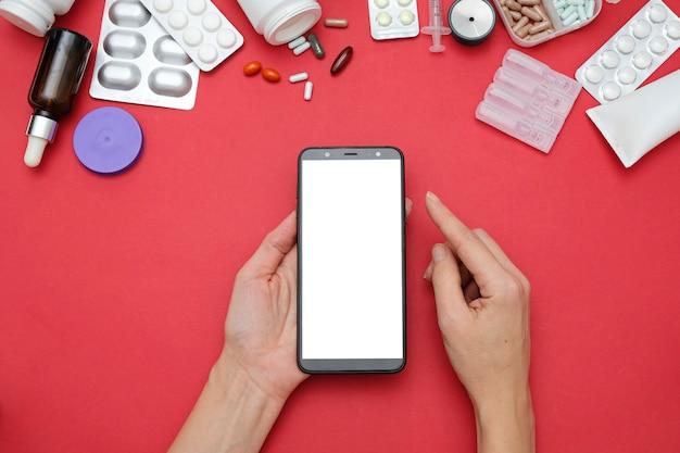 Conceito on-line de farmácia e drogaria. pílulas de medicina e smartphone nas mãos, espaço para texto
