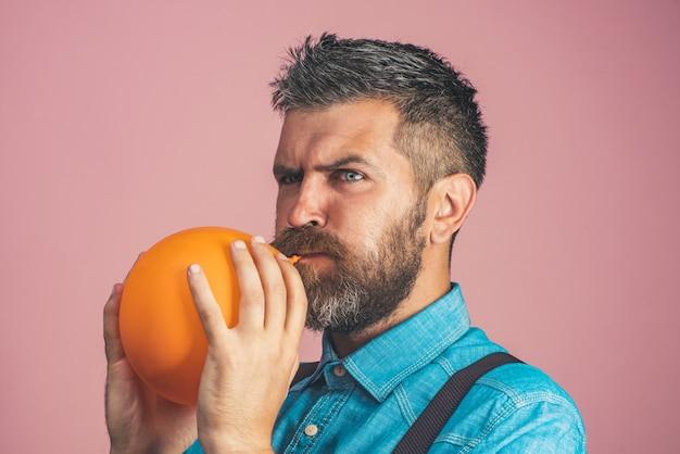 Conceito para a celebração do feliz aniversário, o pai feliz está soprando um balão laranja bonito homem barbudo