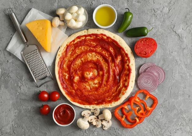 Conceito para cozinhar pizza com ingredientes na mesa cinza