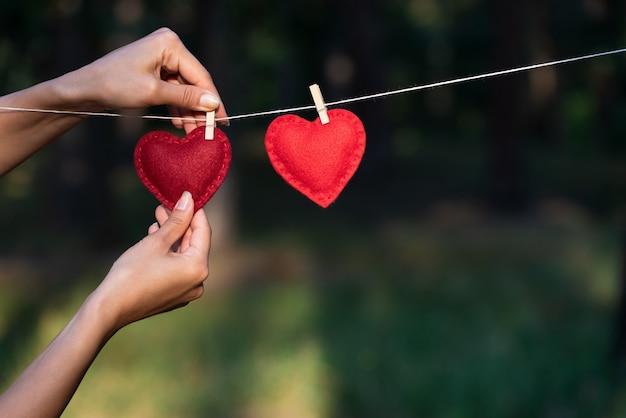 Conceito para o dia dos namorados com espaço de cópia para o texto. a garota confessa que está apaixonada. dois corações vermelhos no fundo da natureza