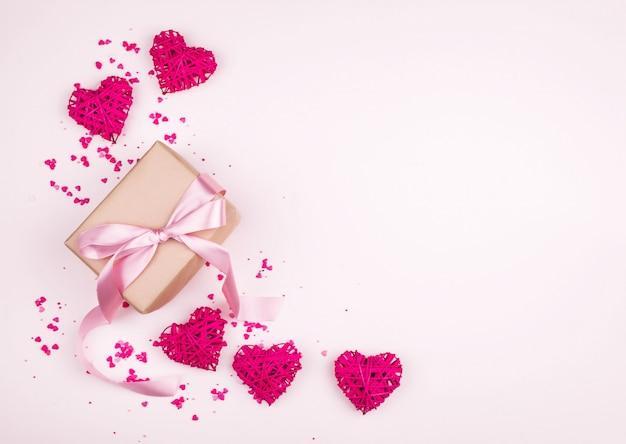 Conceito para o feriado de todos os amantes, um lugar para escrever, uma vista de cima. corações, fundo suave, presente, mãos.