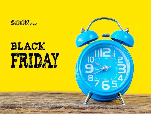 Conceito preto da venda do tempo de sexta-feira, despertador azul com fundo amarelo.