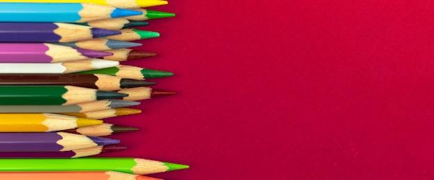 Conceito pronto para desenhar, fundo de banner com lápis de cor em uma área de trabalho vermelha, espaço de cópia, foto de vista superior