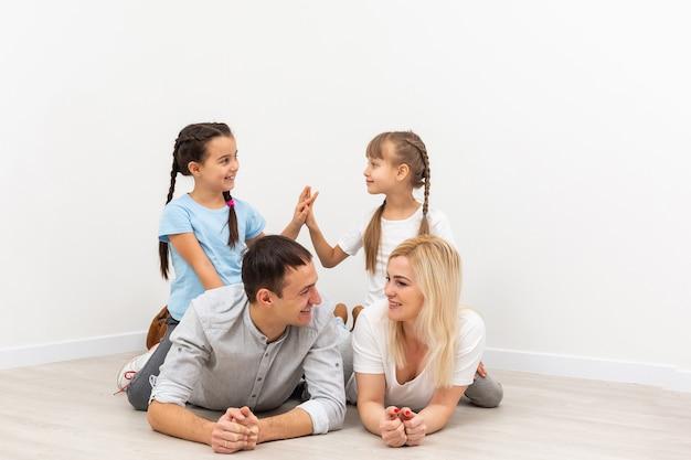 Conceito que abriga uma jovem família. mãe, pai e filhos em uma nova casa