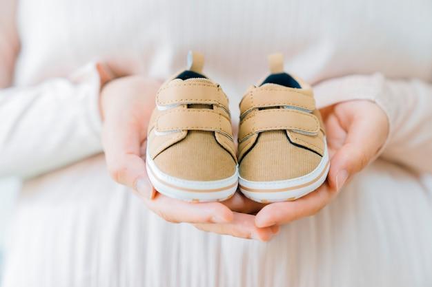 Conceito recém nascido com mãos segurando sapatos