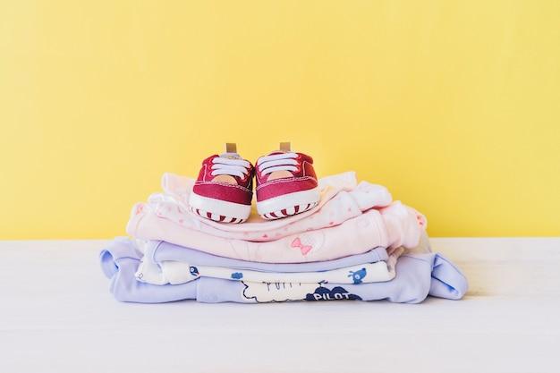 Conceito recém-nascido com pilha de roupas