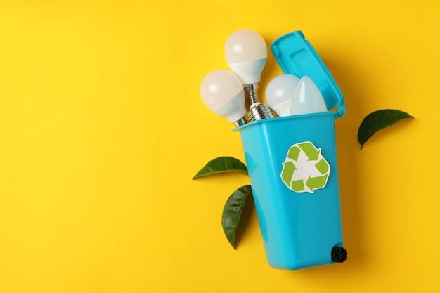 Conceito reciclado de energia verde sobre fundo amarelo.